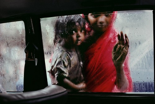 "INDIA-10214, Bombay, India Mother and Child at Car Window, Bombay/Mumbai, India, 1993 A mother and child beg for alms through a taxi window during the monsoon. Bombay is the capital of India's business, movie, music, and fashion worlds. A city of wealth, but everywhere, within a few steps, is the greater India. Poverty, for both its victims and those who only witness it, is inescapable. Refugees from India's rural poverty and people seeking opportunities for a better life arrive each day in the thousands to swell a city which already seems to burst at the seams. Over time, you learn of the complex economics of Bombay's beggars. Street corners can be ""inherited"" or subject to leasing arrangements; a spot on one intersection busy with taxis is prime real estate. Begging is a way of life. An overwhelming number of the city's inhabitants live on the streets in intricate hierarchies-those that have shelter are better off than those on open ground. They in turn have risen above those who live on the streets themselves. (2000) South SouthEast. London: Phaidon Press Limited, 43. National Geographic, March 1995, Bombay: India's Capital of Hope Magnum Photos, NYC5919, MCS1996002 K097 ..Phaidon, 55, South Southeast, Iconic Images, final book_iconic, final print_milan Jam-packed and alive with commerce, India's richest country allures new corners by the hundreds each day. Arriving with little more than dreams, some hit it big. Others remain on the outside looking in: half of Bombay's 13 million people live on the streets or in ramshackle huts, and thousands-like this woman and child-survive only by begging. National Geographic: John McCarry (March 1995) Bombay: India's Capital of Hope, National Geographic. (vol.187 (3)) pp.42-67 *See caption in book. Iconic Photographs"